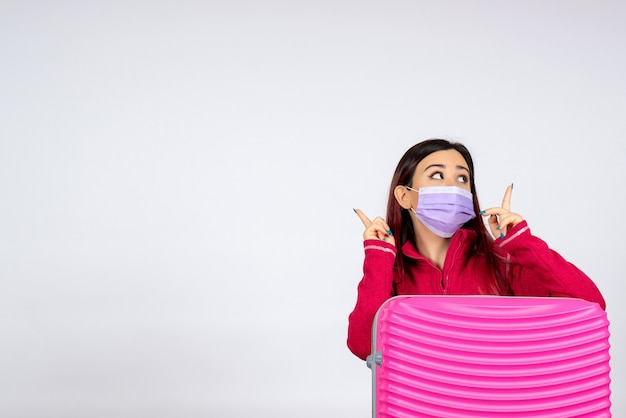 Widok z przodu młoda kobieta z różową torbą w masce na białej ścianie wakacje z wirusem pandemicznym w kolorze