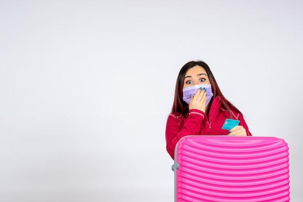 Widok z przodu młoda kobieta z różową torbą w masce trzymając kartę bankową na białej ścianie kobieta wirusowa pandemia podróży kolorami