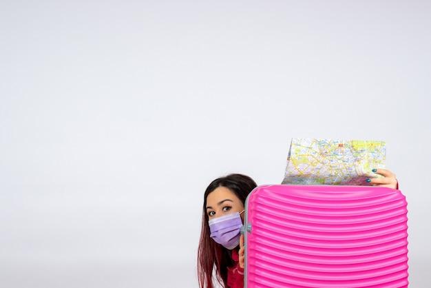 Widok z przodu młoda kobieta z różową torbą w masce trzymającej mapę na białej ścianie kobieta kolor wirus wakacje pandemiczna wycieczka covid-
