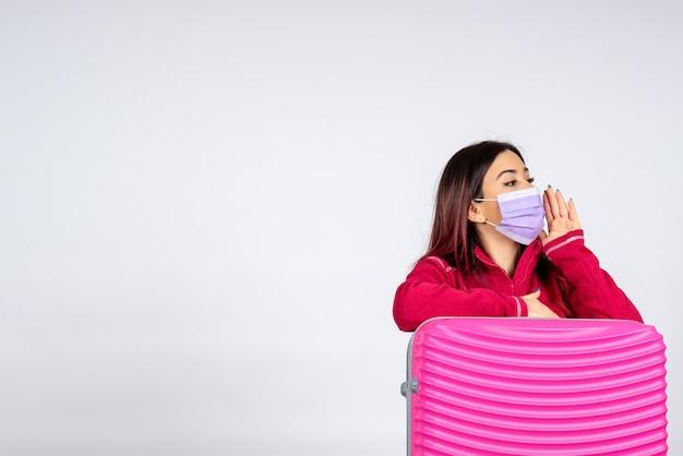 Widok z przodu młoda kobieta z różową torbą w sterylnej masce wzywająca na białą ścianę wycieczka kolorowa wakacje covid - pandemia wirusa kobiety