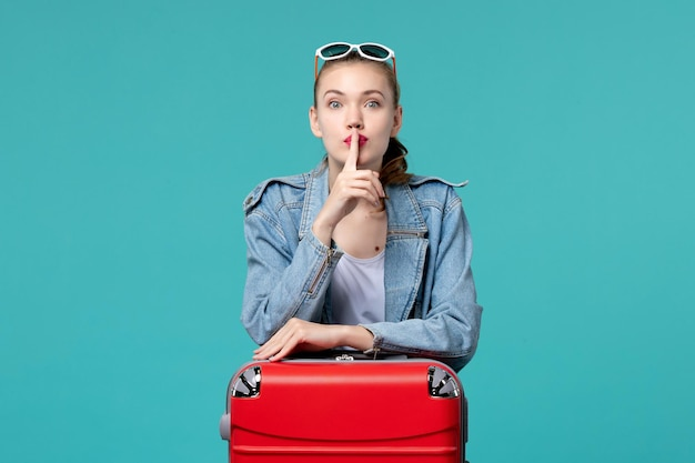 Widok z przodu młoda kobieta z torbą przygotowuje się do wakacji i prosi o ciszę na niebieskiej przestrzeni