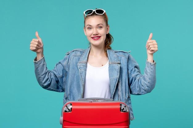 Widok z przodu młoda kobieta z torbą przygotowuje się do wakacji na niebieskiej przestrzeni