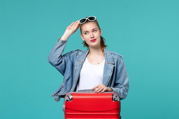Widok z przodu młoda kobieta z torbą przygotowuje się do wakacji na niebieskim biurku