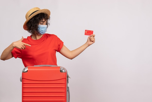 Widok z przodu młoda kobieta z torbą w masce trzymająca czerwoną kartę bankową na białym tle słońce covid pandemia wakacje wycieczka turystyczna kolor pieniądze