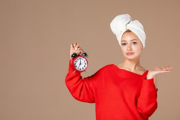 Widok z przodu młoda kobieta z zegarem i ręcznikiem na głowie na różowym tle