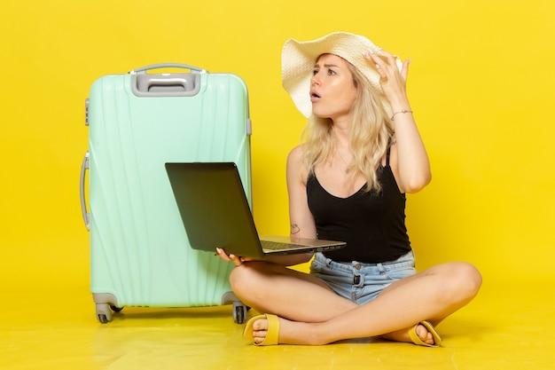 Widok z przodu młoda kobieta za pomocą laptopa na żółtym biurku dziewczyna podróż podróż wakacje podróż słońce