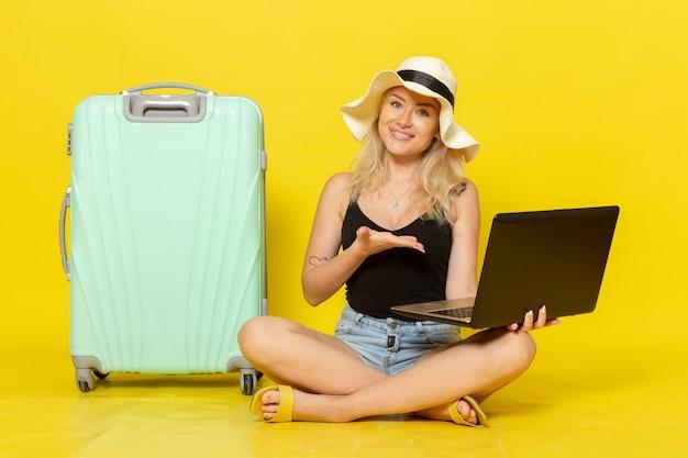 Widok z przodu młoda kobieta za pomocą laptopa na żółtym biurku dziewczyna podróż wakacje podróż podróż słońce