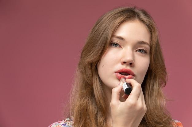 Widok z przodu młoda kobieta za pomocą szminki i patrząc na prosto