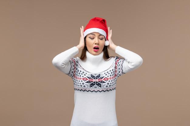 Widok z przodu młoda kobieta zakrywająca uszy na brązowym tle emocji świąt bożego narodzenia