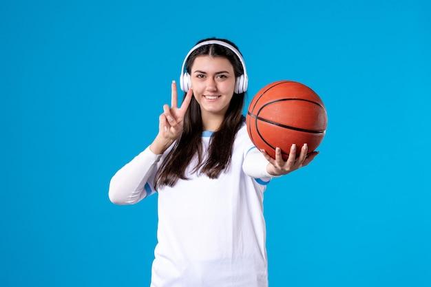 Widok z przodu młoda kobieta ze słuchawkami trzymając koszykówkę na niebieskiej ścianie