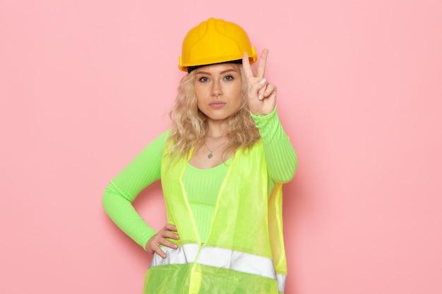 Widok z przodu młoda konstruktorka w zielonym kasku kombinezonu budowlanego przedstawiająca znak zwycięstwa na różowej przestrzeni