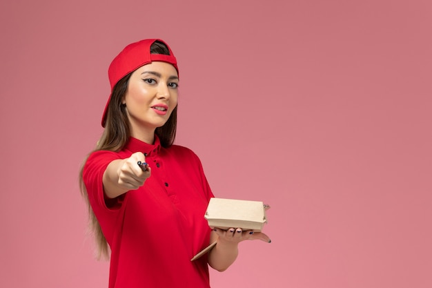 Widok z przodu młoda kurierka w czerwonej pelerynie mundurowej z małym opakowaniem żywności dostawy i notatnikiem z długopisem na rękach na jasnoróżowej ścianie
