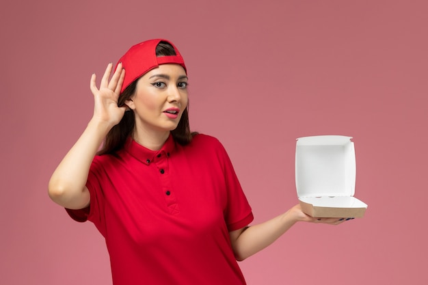 Widok z przodu młoda kurierka w czerwonym mundurze i pelerynie z małym pakietem żywności na rękach, próbująca usłyszeć na jasnoróżowej ścianie