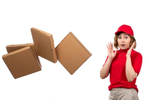 Widok z przodu młoda kurierka w mundurze zaskoczona przed wyrzuconymi paczkami z dostawą