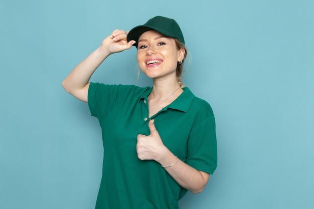 Widok z przodu młoda kurierka w zielonym mundurze i zielonej pelerynie pokazująca jak znak z uśmiechem i pozująca na niebieskiej dziewczynie pracy kosmicznej
