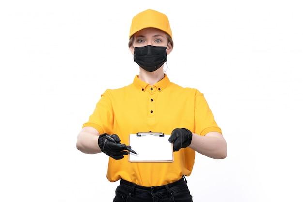 Widok z przodu młoda kurierka w żółtych mundurach czarnych rękawiczkach i czarnej masce trzymająca notatnik z prośbą o podpis