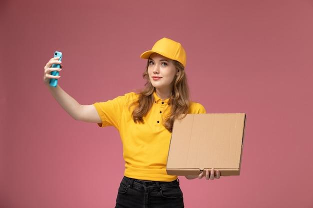 Widok z przodu młoda kurierka w żółtym mundurze, trzymająca pudełko z jedzeniem, robiąca z nim zdjęcie na ciemnoróżowym biurku, mundurowy pracownik kurierski