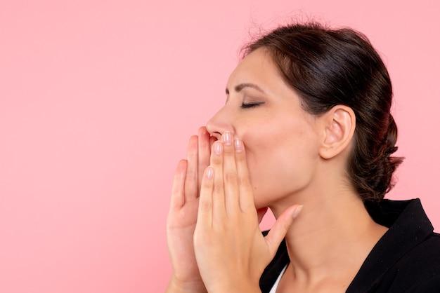 Widok z przodu młoda ładna kobieta dzwoniąc na różowym tle