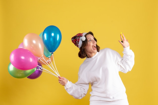 Widok z przodu młoda ładna kobieta trzyma balony na żółty nowy rok emocja boże narodzenie kobieta kolor