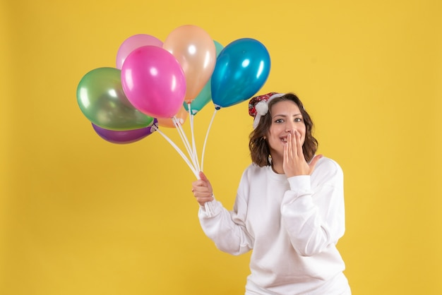 Widok z przodu młoda ładna kobieta trzyma balony na żółty nowy rok emocje boże narodzenie kolor kobieta