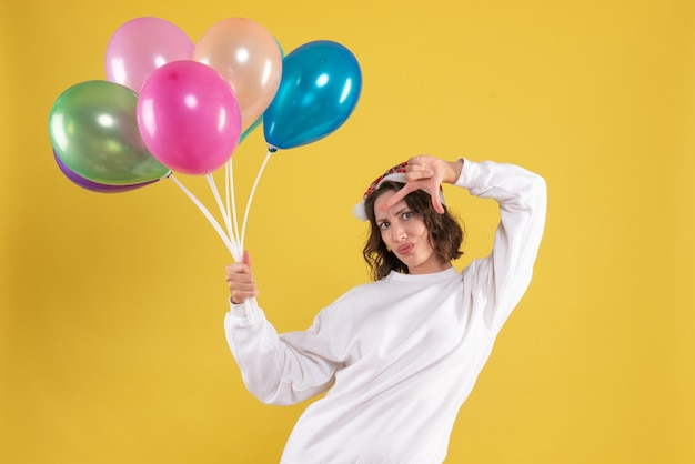 Widok z przodu młoda ładna kobieta trzyma balony na żółtym boże narodzenie kobieta nowy rok kolor emocji