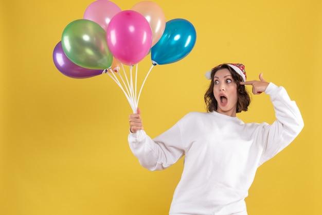 Widok z przodu młoda ładna kobieta trzyma balony na żółtym boże narodzenie nowy rok kobieta kolor emocji