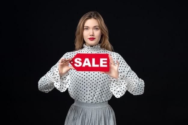 Widok z przodu młoda ładna kobieta trzyma czerwoną wyprzedaż pisanie na czarnej ścianie kolor zakupy moda zdjęcie kobieta emocja