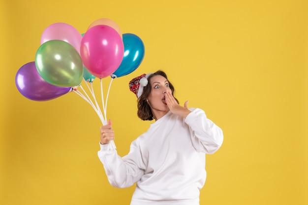 Widok z przodu młoda ładna kobieta trzyma kolorowe balony na żółty nowy rok emocji kolor kobiety boże narodzenie