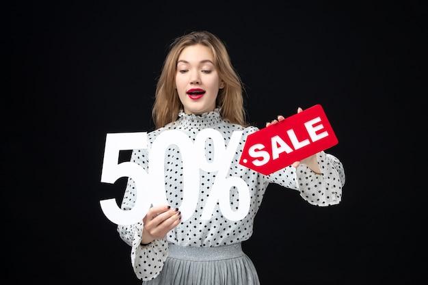 Widok z przodu młoda ładna kobieta trzyma sprzedaż pisanie i na czarnej ścianie kolor zakupy moda emocje uroda wakacje boże narodzenie