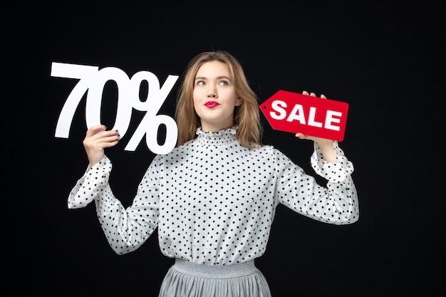 Widok z przodu młoda ładna kobieta trzyma sprzedaż pisanie i na czarnej ścianie kolor zakupy moda zdjęcie emocje model piękna