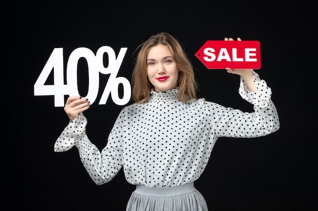 Widok z przodu młoda ładna kobieta trzyma sprzedaż pisanie i na czarnej ścianie kolor zakupy świąteczne emocje moda wakacje