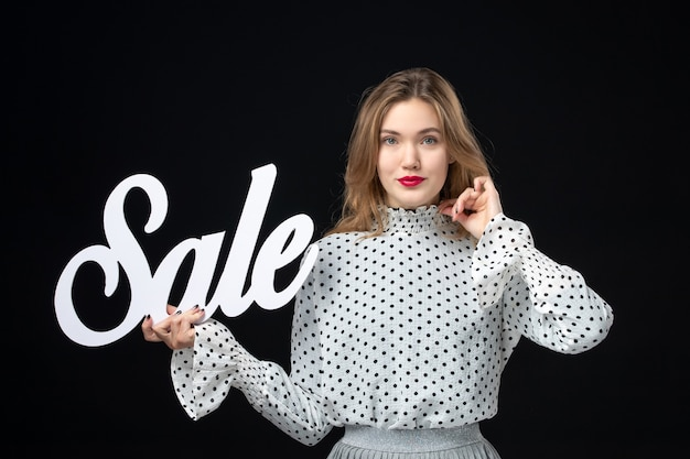 Widok z przodu młoda ładna kobieta trzyma sprzedaż pisanie na czarnej ścianie kolor zakupy uroda modelka moda zdjęcia emocje fashion