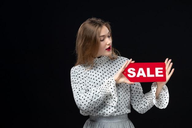Widok z przodu młoda ładna kobieta trzyma sprzedaż pisanie na czarnej ścianie model emocja zakupy moda kobieta uroda kolor