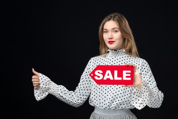 Widok z przodu młoda ładna kobieta trzyma sprzedaż pisanie na czarnej ścianie model piękna emocja czerwony moda kobieta kolor