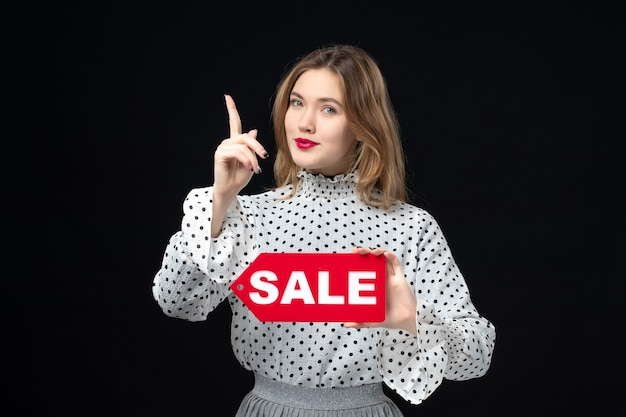 Widok z przodu młoda ładna kobieta trzyma sprzedaż pisanie na czarnej ścianie model uroda emocja zakupy kobieta kolor czerwony