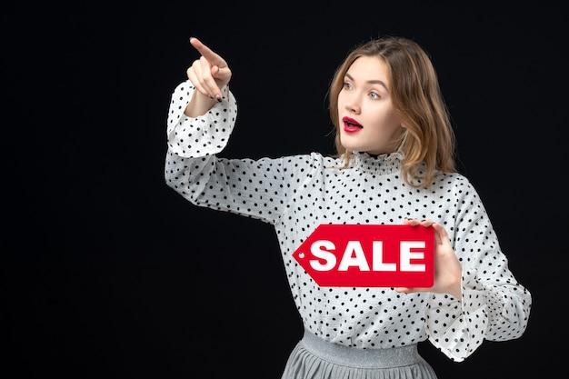 Widok z przodu młoda ładna kobieta trzyma sprzedaż pisanie na czarnej ścianie model uroda emocje zakupy moda kobieta kolor