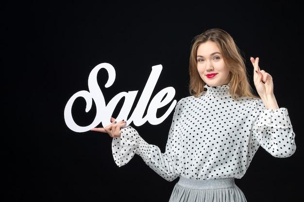 Widok z przodu młoda ładna kobieta trzyma sprzedaż pisanie na czarnej ścianie zakupy uroda moda emocje kolor model zdjęcie