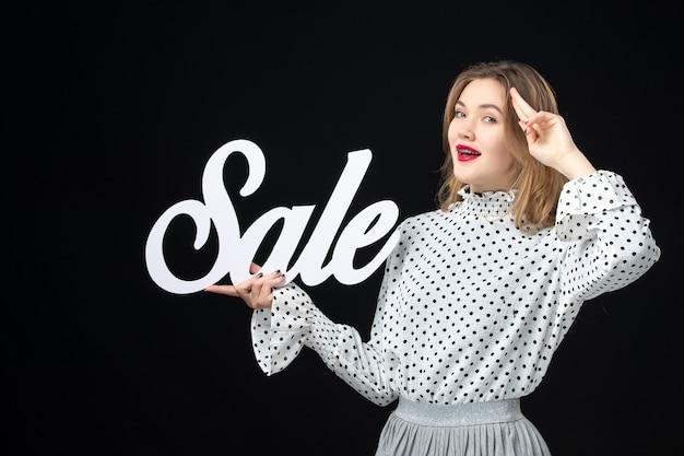 Widok z przodu młoda ładna kobieta trzyma sprzedaż pisanie na czarnej ścianie zakupy uroda moda emocje kolory model zdjęcie