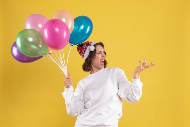 Widok z przodu młoda ładna kobieta trzymając balony na kolor żółty boże narodzenie nowy rok emocja kobieta