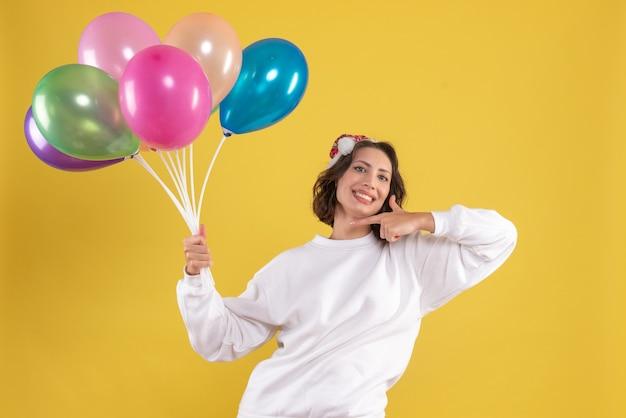 Widok z przodu młoda ładna kobieta trzymając balony na żółtym kolorze boże narodzenie kobieta emocji nowego roku