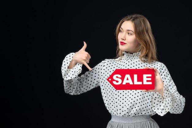 Widok z przodu młoda ładna kobieta trzymająca sprzedaż pisanie na czarnej ścianie modelka uroda emocja czerwona zakupy moda kobieta