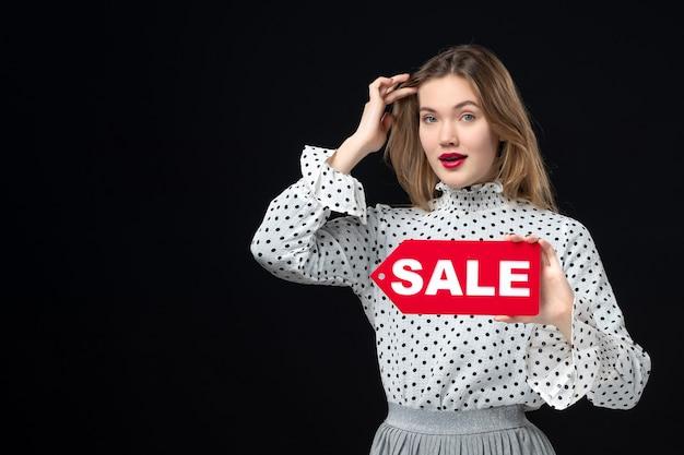 Widok z przodu młoda ładna kobieta trzymająca sprzedaż pisanie na czarnej ścianie modelka uroda emocje czerwone zakupy fotografia moda kobieta kolor