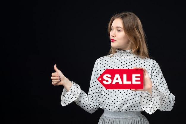 Widok z przodu młoda ładna kobieta trzymająca sprzedaż pisanie na czarnej ścianie modelka uroda emocje czerwony zakupy moda kobieta kolor