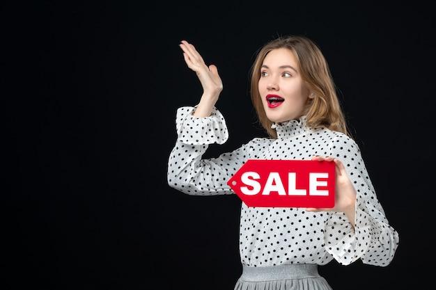 Widok z przodu młoda ładna kobieta trzymająca wyprzedaż pisanie na czarnej ścianie czerwony kolor zakupy zdjęcie emocja moda kobieta