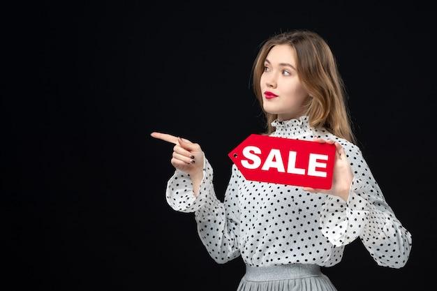 Widok z przodu młoda ładna kobieta trzymająca wyprzedaż pisanie na czarnej ścianie kolor zakupy moda zdjęcie kobieta emocje czerwony