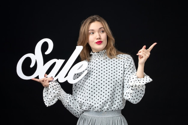 Widok z przodu młoda ładna kobieta trzymająca wyprzedaż pisanie na czarnej ścianie kolor zakupy uroda emocja model fotografia moda
