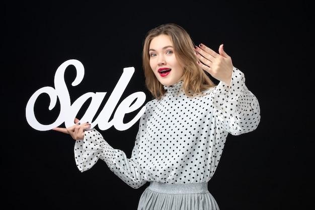 Widok z przodu młoda ładna kobieta trzymająca wyprzedaż pisanie na czarnej ścianie zakupy piękno emocja kolor model fotografia moda