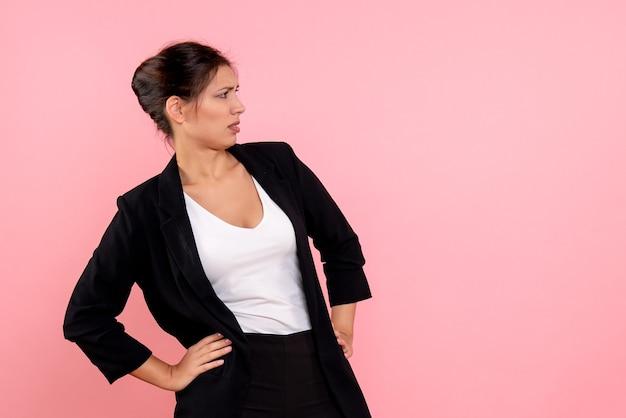 Widok z przodu młoda ładna kobieta w ciemnej kurtce na różowym tle