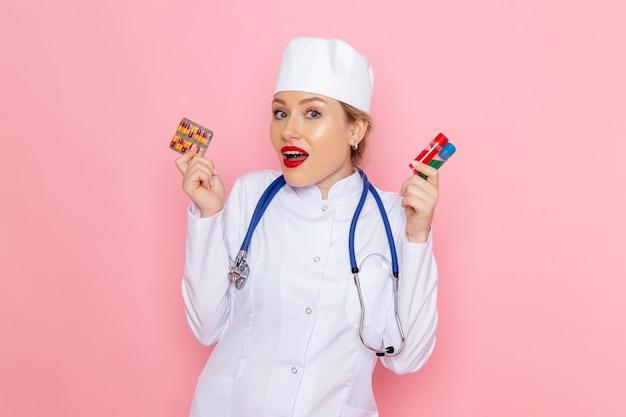 Widok z przodu młoda lekarka w białym garniturze medycznym z niebieskim stetoskopem trzymająca pigułki i kolby na różowym szpitalu medycznym medycyny kosmicznej