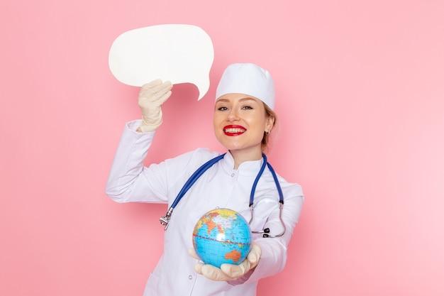 Widok z przodu młoda lekarka w białym garniturze medycznym z niebieskim stetoskopem trzymającym globus i biały znak uśmiechnięty na różowej przestrzeni medycyna szpital medyczny zdrowie
